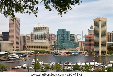 Baltimore city inner harbor showing the city skyline, ship, and pleasure craft docks and boardwalk.