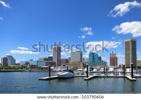 Baltimore Maryland downtown business district skyline scenic cityscape panoramic with pleasure boats in port marina at Inner Harbor over blue sky