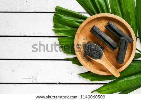 Bamboo charcoal and powder on wooden table. copy space