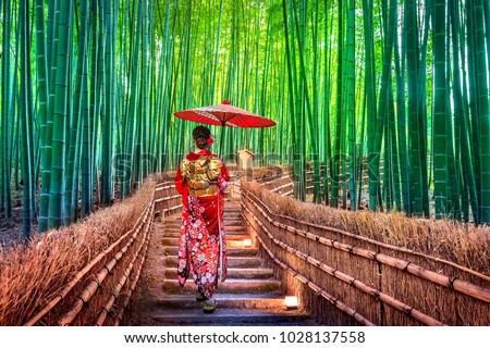 Photo of Bamboo Forest. Asian woman wearing japanese traditional kimono at Bamboo Forest in Kyoto, Japan.
