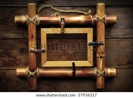 Bamboo frame on wooden background - stock photo