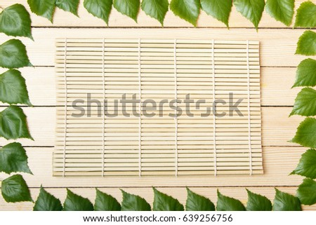 Bamboo mat, top view, on a wooden background, framed with leaves of a tree