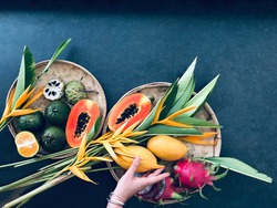 Bamboo plate with exotic fruits: papaya, mango, dragon fruit on gray background with orange flowers and woman hand