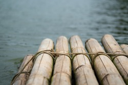 Bamboo rafting stacked which is binding with rope line, it's floating on the lake water. Journey or adventure activity. Transportation object. Selective focus on the rope surface.