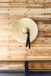 Bamboo rattan wicker hat hanging on the wall sheathed with lath. Asian handcraft. Vintage detail headdress. Summer time. Background