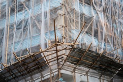 Bamboo scaffolding on building facade, construction site  -