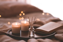 Bamboo sticks in bottle with scented candles and open book on wooden tray in bed closeup. Home aroma.