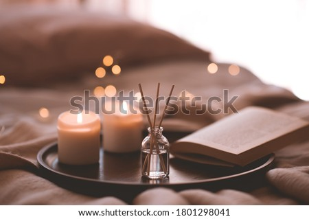Photo of  Bamboo sticks in bottle with scented candlrs and open book on wooden tray in bed closeup. Home aroma.