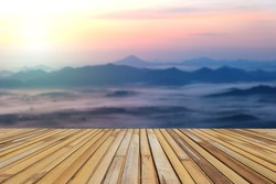 Bamboo table top stands for display product with the blurred mountain and sea of fog landscape background in the morning before sunrise.