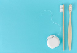 Bamboo toothbrush and dental floss on blue background. Dental care concept