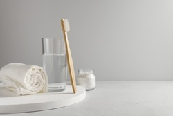 Bamboo toothbrush, glass of water, white a cotton towel and powder for brushing your teeth in jar. light gray concrete surface, gray backdrop. Biodegradable personal care products. No plastic concept.