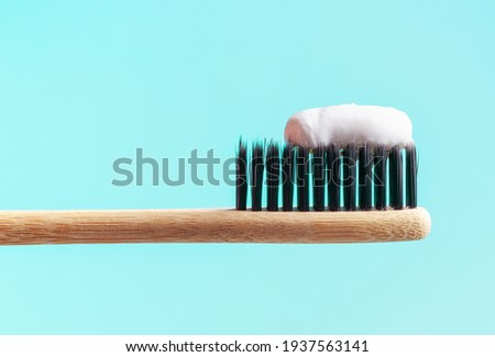 Bamboo toothbrush with toothpaste on a blue background close up. Photo stock ©