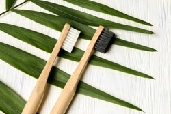 bamboo toothbrushes on white wood background with tropical leaf. Place for text. Ecoproduct.   eco-friendly