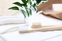 Bamboo toothbrushes with towel, soap and green leafs