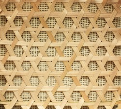 Bamboo wickerwork of strawberry basket from market place, burlap textile in the background.