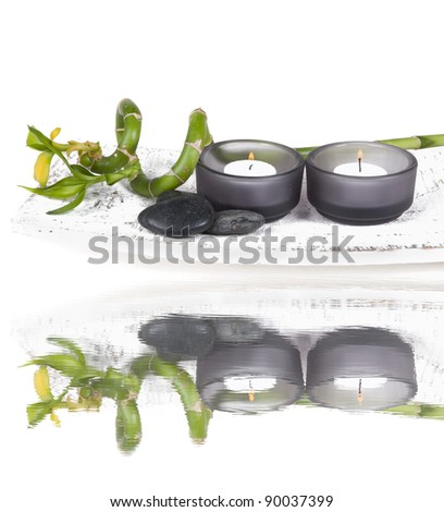 Bamboo with candles and Zen stones on a white washed plate