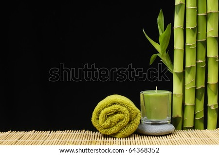 Bamboo, zen stones and candle with towel on the black background