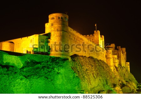 Bamburgh Castle at night close up / Bamburgh Castle at night illuminated by green and golden lights