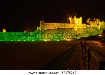 Bamburgh Castle at night with fence / Bamburgh Castle at night illuminated by green and golden lights