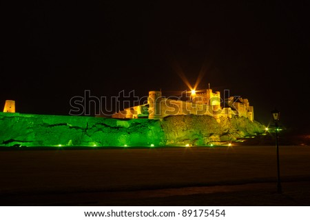 Bamburgh Castle at night with lamp post / Bamburgh Castle at night illuminated by green and golden lights