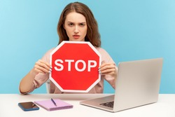 Ban, forbidden access! Young woman holding stop symbol, warning with red traffic sign and looking angrily, sitting at workplace with laptop, home office. indoor studio shot isolated on blue background