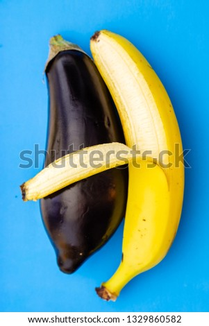 Banana and eggplant on blue background. Banana hugs eggplant. The skin of a banana resembles a hand. The concept of gay relationships. LGBT family. Interracial relationship. Black and white gay couple