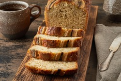 Banana bread. Cake with banana, traditional american cuisine. Slices of loaf. Dark background, black table.