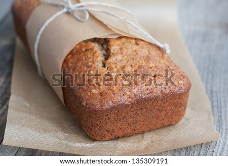 Banana bread with nuts in the baking paper on the wooden table, selective focus