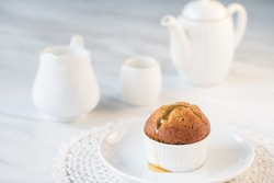 Banana cupcake with honey on top in white ceramic cup with white teapot and tea of cup  on marble background copy space selective focus