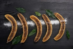 Banana dessert with mint on black background table. Traditional Thai and Asian recipe menu restaurant, Horizontal photo with black background and text area or menu design. Top view, flat, overhead.