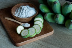 Banana flour with slice and whole green raw bananas on a wooden cutting board, prebiotic food for gut health.