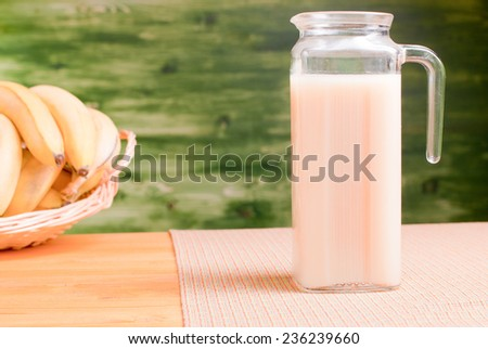 banana juice in the decanter on a yellow table with a napkin on zalenom background bananmi side view