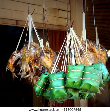 banana leaf packages containing a fish snack for sale in asia on a market