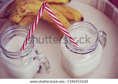 Banana milkshake in glasses with straw #1186055620