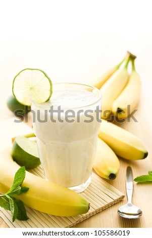 Banana milkshake or smoothie with bananas on wood