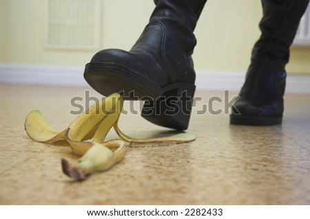 Banana skin lies ready to cause a painful slip-up. Slapstick concept illustrating danger and pitfalls.