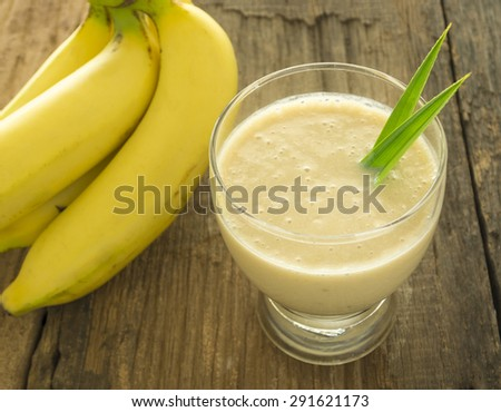 Banana smoothie in a glass is placed on a wooden table.