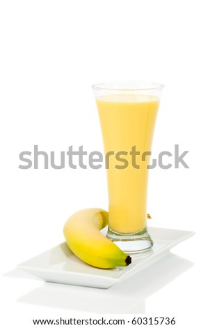 Banana smoothie in tall glass on white background