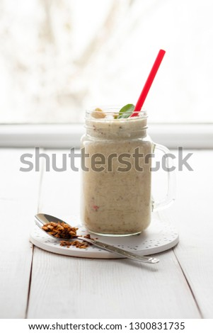 Banana smoothie with peanut butter, cinnamon and granola #1300831735