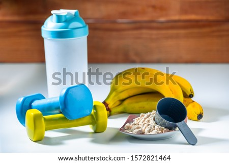 Banana Whey Protein Powder With Shacker and Two Dumbells