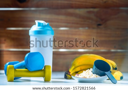Banana Whey Protein Powder With Shaker and Two Dumbells