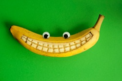 Banana with toy eyes and with a smile against a green background