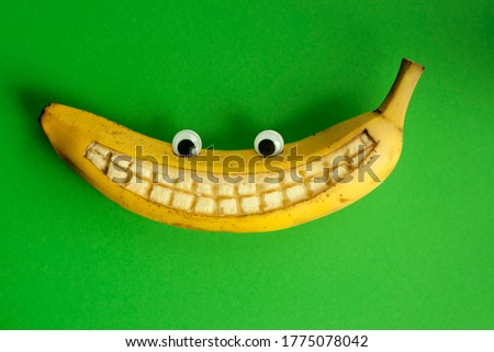 Banana with toy eyes and with a smile against a green background Stock photo ©