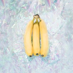 Bananas in iridescent neon background. Abstract holographic soft pastel colors backdrop. Hologram aesthetic foil. Trendy vaporwave creative gradient. Retro futurism.