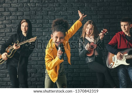Band of teenage musicians playing against dark wall #1370842319