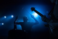 Band performing live during concert, gig. Guitarist and drummer silhouettes