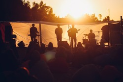 Band playing gig on a beach to the resting people in a warm sunset lights