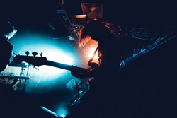 Band Silhouette. View of stage during rock concert with musical instruments and scene stage lights, rock show performance. Guitarist plays solo on stage. Electric guitar.