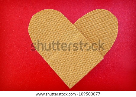 bandage in a heart shape, on red textured background