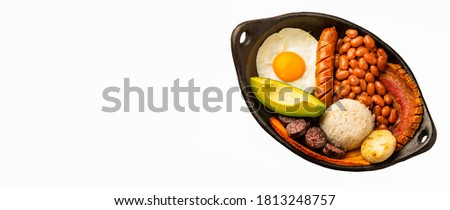 Bandeja paisa, typical dish at the Antioqueña region of Colombia. It consists of chicharrón (fried pork belly), black pudding, sausage, arepa, beans, fried plantain, avocado egg, and rice Foto stock ©